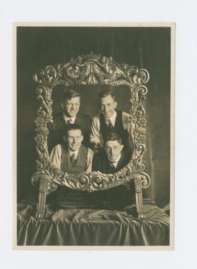 Underhill office crew looking through carved frame; clockwise from top left Frank Riedel (upholstery shop), Richard Pitman (draughtsman), Ralph W. Armitage (architect), and William Hickman (bookkeeper)