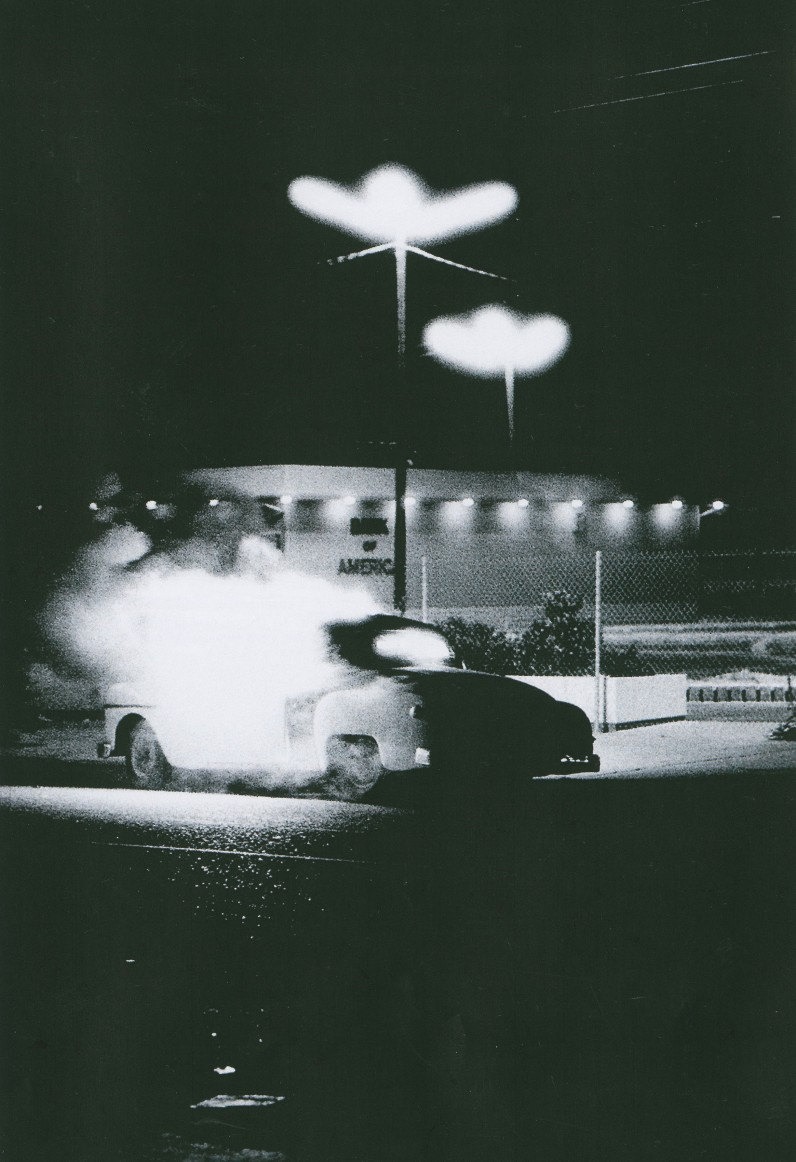 Joseph S. Melchione; Car burning in front of Bank of America's temporary branch; gelatin silver print; 25 ½ x 21 ½ in; ©The Estate of Joseph S. Melchione.